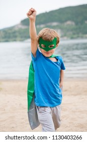 Happy child in Superhero's costume playing in the beach.