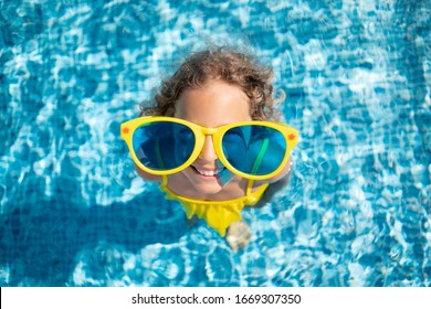 Happy child in swimming pool. Girl having fun on summer vacation. Top view portrait