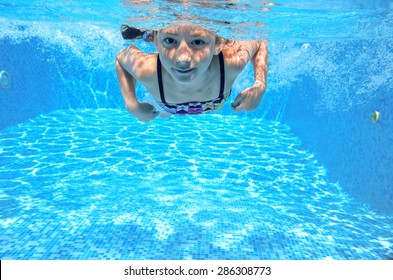 Happy child swims in pool underwater, active kid swimming, playing and having fun, children water sport