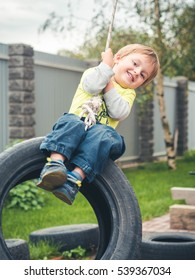 Happy child swinging on a car tire used as a swing. Concept photo of childhood, nostalgia, memory, past, life, retro, vintage, home sweet home.