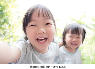 Happy child take a selfie in the park, asian