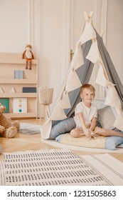 Happy child in tent and rug in white playroom interior with plush toy on wooden shelf. Real photo