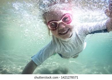 Happy child toddler swimming underwater during summer beach holidays vacation