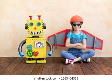 Happy child with toy robot. Funny kid playing at home. Success, creative and innovation technology concept