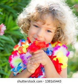 Happy child with tropic flower. Summer vacations concept