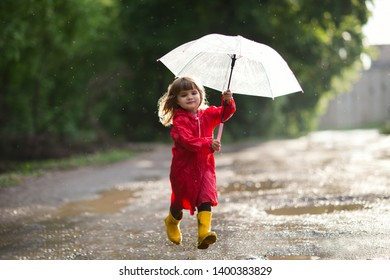 Happy child  with an umbrella playing also walks on pools in the summer outdoors