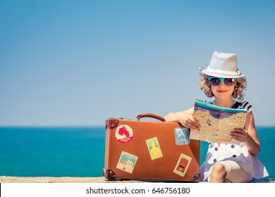 Happy child with vintage suitcase and city map. Kid having fun on summer vacation. Travel and adventure concept