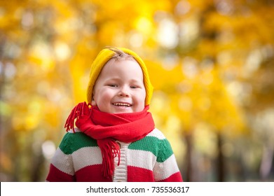 Happy child walking in autumn park. Healthy smiling boy Colorful and bright nature. Family outdoors. Kid with red scarf on neck.
