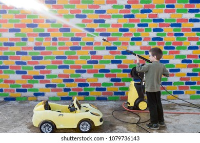 Happy child washes yellow toy car from high pressure washer in front of multi-colored brick wall. Fun during summer holidays. Concept of family business.