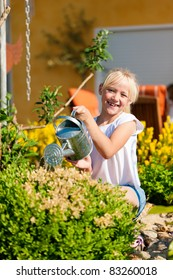 Happy child watering flowers in the garden in front of her home