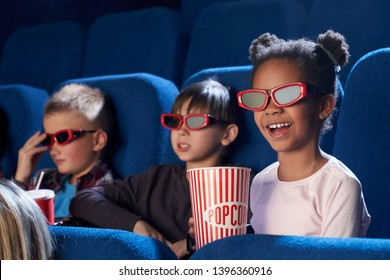 Happy child wearing 3d glasses, eating tasty popcorn and watching comical movie. Cute little girl spending free time with friends in cinema and laughing. Concept of leisure and entertainment.