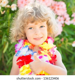 Happy child wearing hawaiian flowers garland showing thumb up sign on the beach. Summer vacations concept