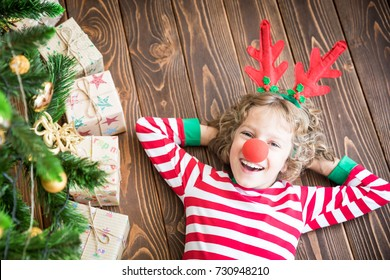 Happy child wearing reindeer Rudolph near Christmas tree. Funny kid on Christmas eve. Xmas holiday concept. Top view portrait