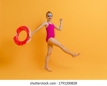 Happy child wearing swimsuit. Girl with swimming ring donut. Kid on a colored yellow background.