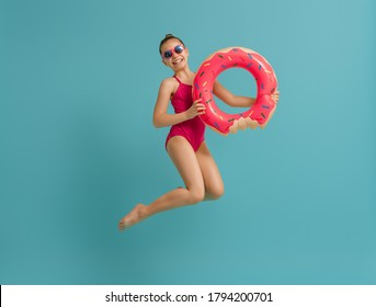 Happy child wearing swimsuit. Girl with swimming ring donut. Kid on a colored teal background.