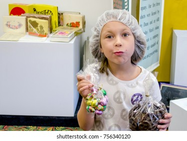 A happy child wears a hair net after touring a candy factory. With chocolate in both hands, her expression shows she is ready to eat it now!