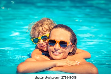 Happy child and woman playing in swimming pool. Summer vacation concept
