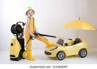 Happy child in yellow overalls and boots with high pressure washer serves client boy on toy car under umbrella. Concept of family business. White background