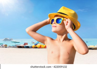 Happy child in yellow sunglasses on beach. Summer vacation concept