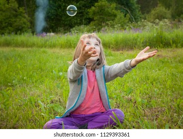 Happy childhood: adorable joyful preschooler girl playing with soap bubbles sitting in a summer park