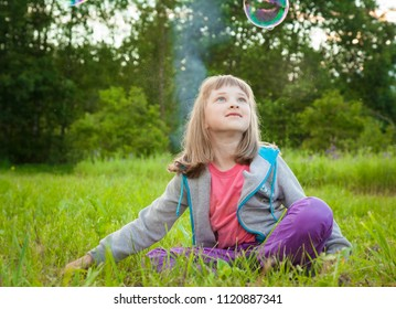Happy childhood: adorable preschooler girl playing with soap bubbles sitting in a summer park