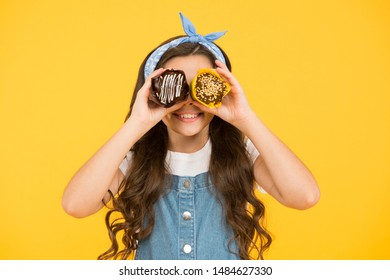 Happy childhood. Adorable smiling child with cupcakes on yellow background. Treat someone with sweets. Yummy cupcakes. Bakery confectionery concept. Kid girl hold glazed muffins. Delicious cupcakes.