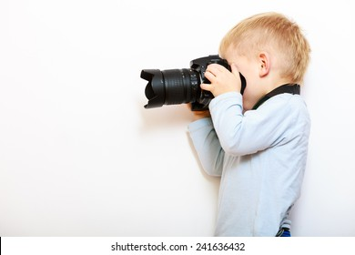 Happy childhood. Boy child kid playing with camera. Preschooler taking picture at home. Real photo.