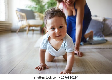Happy childhood concept. Picture of lovely sweet 1 year old baby boy crawling along wooden floor in living room, having curious expression, his young mom in background helping him. Film effect