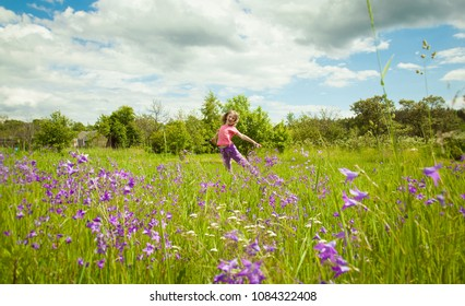 Happy childhood - cute little girl jumping on a green summer meadow