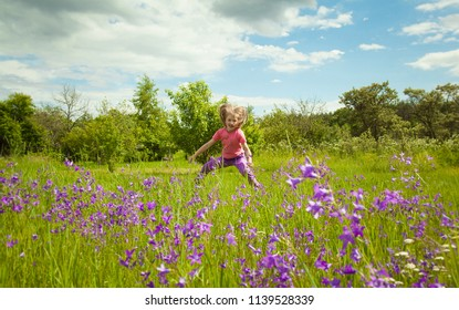 Happy childhood - cute little girl jumping in a green summer meadow