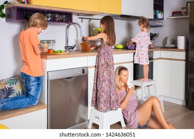 Happy childhood, family, fun and entertainment concept. Candid shot of three children siblings cooking together in kitchen standing barefooted while mom is resting