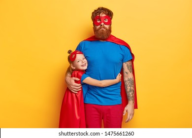 Happy childhood and fatherhood concept. Smiling small redhead female kid embraces with love father, wears bright superhero costume, come together on children parrty, pretend being supernatural.