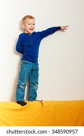Happy childhood. Full length funny boy child kid preschooler standing playing on top of sofa. At home.