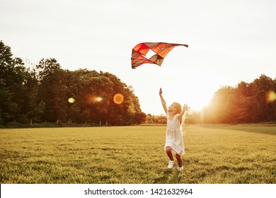 Happy childhood. Happy girl in white clothes have fun with kite in the field. Beautiful nature.