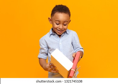 Happy childhood, joy and celebration concept. Cheerful fashionable dark skinned boy in blue shirt opening box with gift received from his friend. Cute black child overjoyed with birthday present