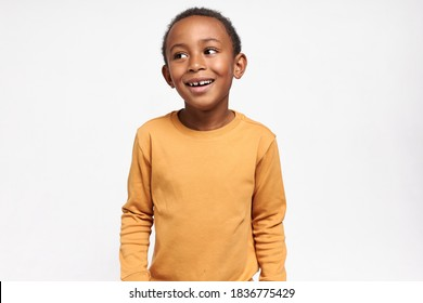 Happy childhood, joy and positive emotions. Isolated shot of cute black child with shirt curly hair looking away with excited facial expression, smiling, having fun, playing games with friends