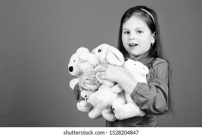 Happy childhood. Little girl play with soft toy teddy bear. Lot of toys in her hands. Collecting toys hobby. Cherishing memories of childhood. Childhood concept. Small girl smiling face with toys.