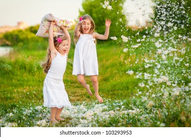 Happy childhood: Little girls having fun with pillows and feathers