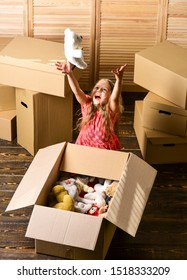 Happy childhood. Relocating family stressful for kids. Box package and storage. Small child prepare toys for relocation. Kid girl relocating boxes background. Relocating concept. Delivery service.