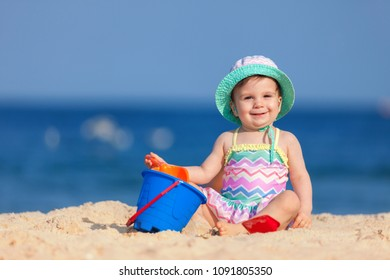Happy childhood vacation. Cute child on the blue sea background. Happy little girl playing with sand on the beach of sea. Summer lifestyle