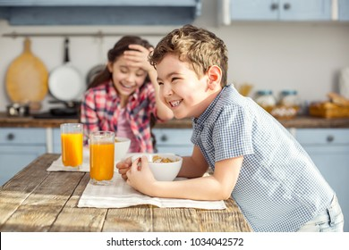 Happy children. Attractive alert little dark-haired boy laughing and having healthy breakfast with his sister and the girl smiling in the background