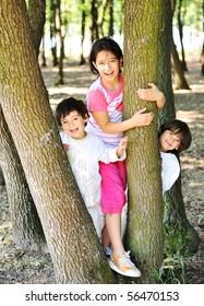 Happy children between the trees in forest