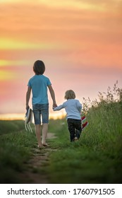 Happy children, boy brothers, holding pair of sneakers in hands, walking on a rural path, barefeet