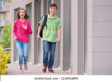 Happy children - boy and girl with backpack on the first or last school day - outdoor portrait. Excited to be back to school after vacation.