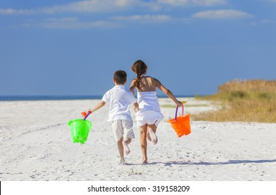 Happy children, boy girl, brother and sister running and having fun playing in the sand on a beach with bucket and spade