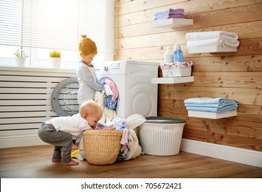 Happy children boy and girl in   in the laundry load a washing machine