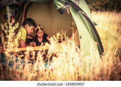 Joyeux enfant garçon et fille jouant ensemble dans une tente de camping sur le site de camping pendant les vacances d'été dans un concept de campagne pour un style de vie d'enfance heureux
