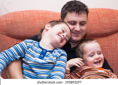 Happy children boys and daddy having fun on sofa at home