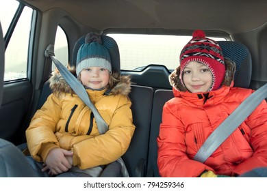Happy children in the car in the back seat winter trip.