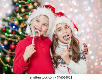 Happy children in christmas caps eating candy canes